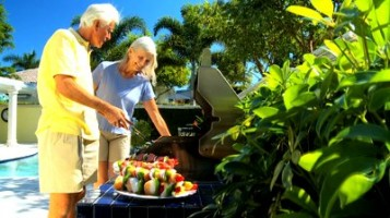 older couple grilling outdoors